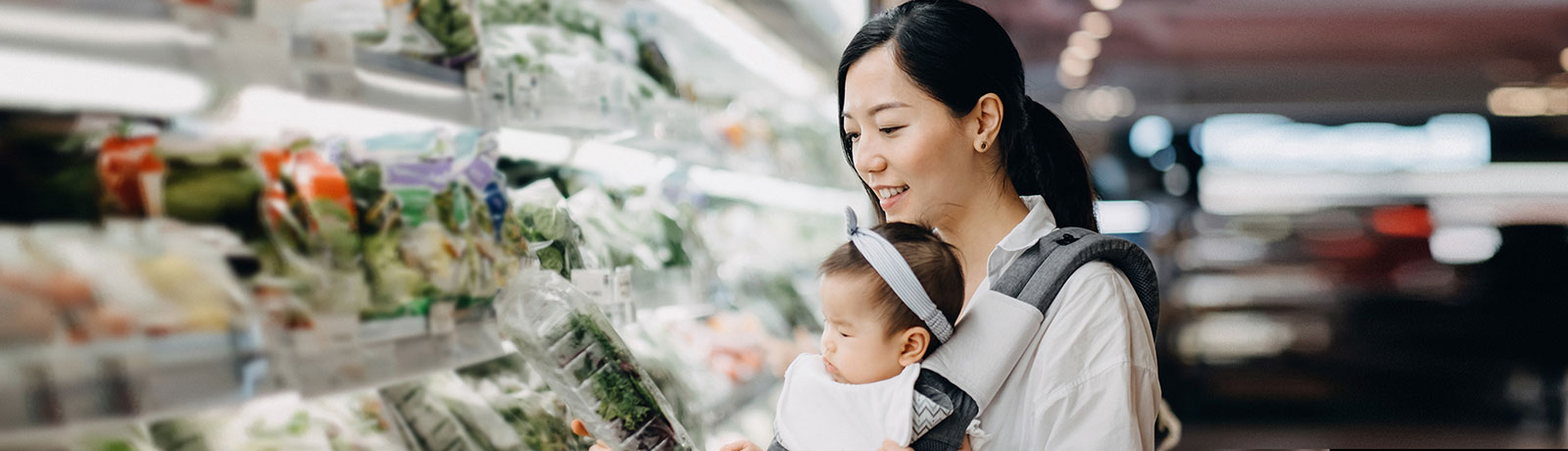 a woman is holding her baby and doing shopping