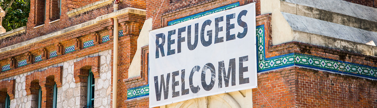 a building with a welcoming refugee banner